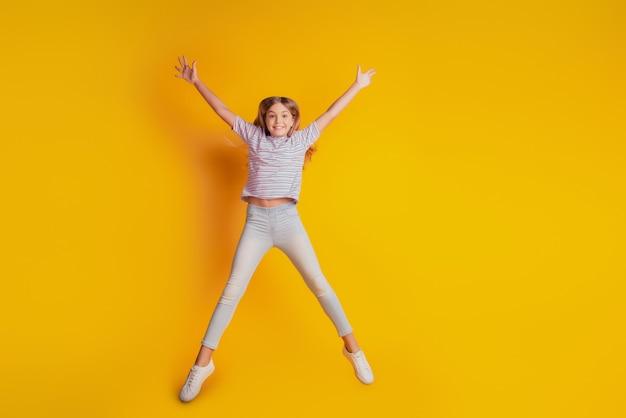 Веселый маленький школьник прыгает высоко изолированный желтый фон