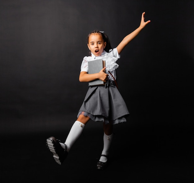 Cheerful little schoolgirl with book and bag going back to school in new season isolated on dark background