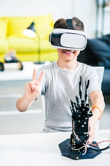 Cheerful little smart boy using his vr glasses while experimenting with humanoid robotic hand at home