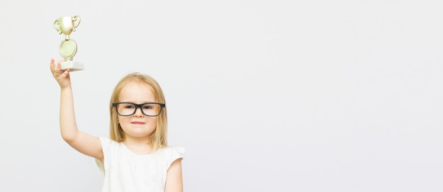 Cheerful little smart girl celebrating the win isolated over white background, wearing glasses showing a trophy