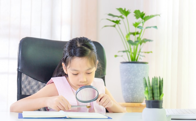 Cheerful little smiling girl learning with a magnifying glass