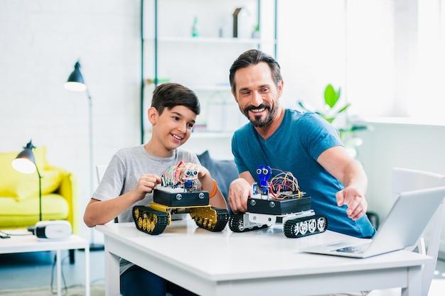 陽気な幼い息子と彼の父親がテーブルに座って、自宅でロボットをテストしています