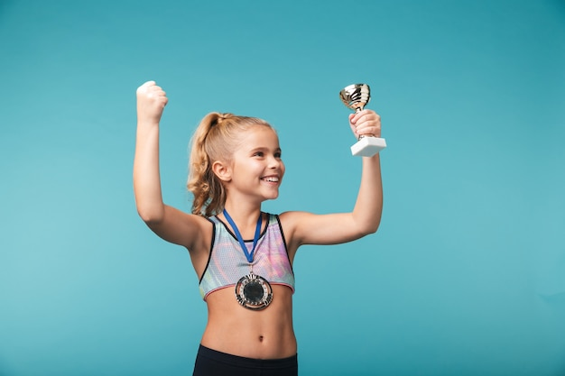 Cheerful little sports girl celebrating the win isolated over blue wall, wearing a gold medal, showing a trophy