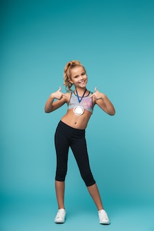 Cheerful little sports girl celebrating the win isolated over blue wall, wearing a gold medal