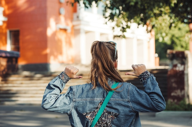 Cheerful little woman in jeans clothes with star on back against blurred city landscape