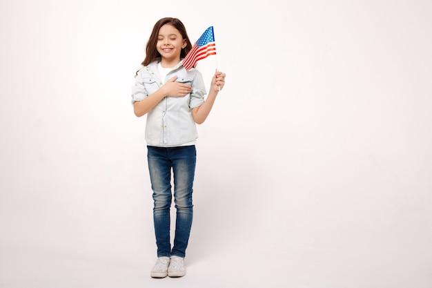 Веселая живая маленькая девочка держит американский флаг и трогает ее грудь, выражая счастье