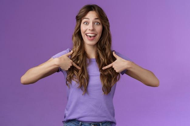 Веселая, жизнерадостная, веселая, веселая, веселая девушка, кудрявая прическа, с открытым ртом, забавляется, указывая центр, сама с радостью рассказывает о своих достижениях, широко улыбаясь, рассказывая друзьям, продвижение по службе фиолетовый фон Бесплатные Фотографии