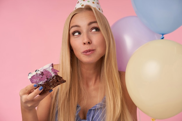 Donna bionda dai capelli lunghi allegra in cappello del cono di vacanza che osserva da parte felicemente mentre mangia la torta di compleanno, festa piacevole di gioia insieme agli amici, stando sopra fondo rosa