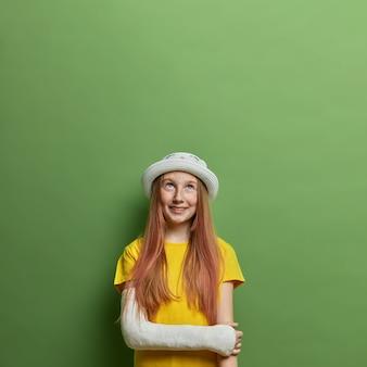 Allegra ragazza adolescente dai capelli lunghi con un braccio rotto in un calco in gesso dopo una spericolata guida in bicicletta, indossa un cappello estivo e una maglietta gialla, guarda felicemente sopra, spera di un rapido recupero. bambini, incidenti