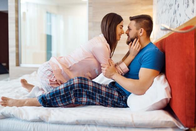 パジャマ姿の陽気な愛のカップルが自宅のベッドで抱擁、おはようございます。若い家族の調和のとれた関係