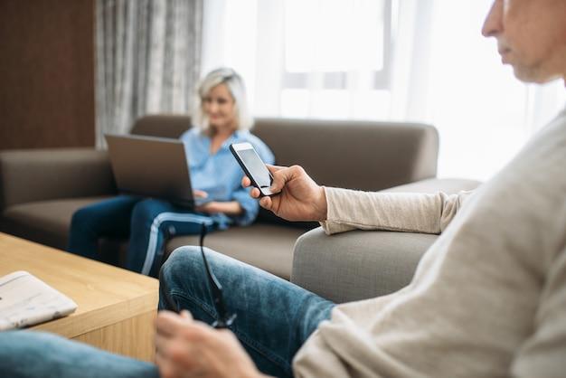 Веселая влюбленная пара отдыхает дома. зрелый муж с мобильным телефоном и жена у ноутбука, счастливая семья отдыхает