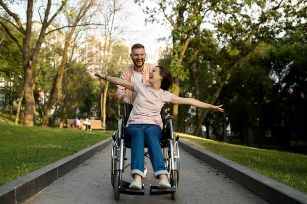 Веселая любовная пара с прогулками в инвалидной коляске в парке