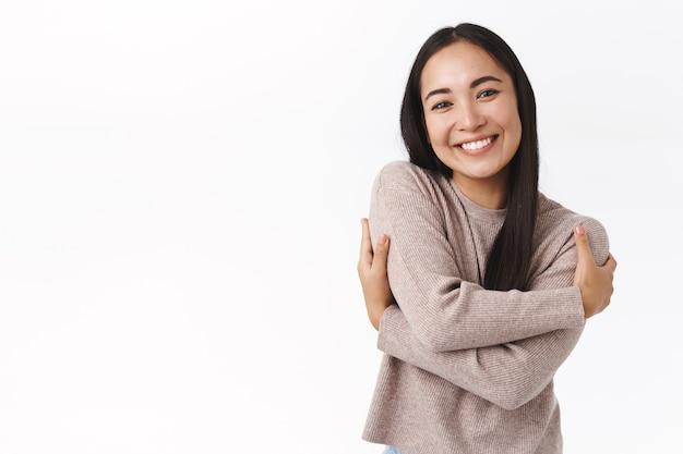 쾌활하고 사랑스러운 아시아 소녀, 아늑한 스웨터를 입은 학생, 자신을 껴안고, 자신의 몸을 껴안고 자기 사랑과 수용을 표현하고 즐겁게 웃고 있습니다.