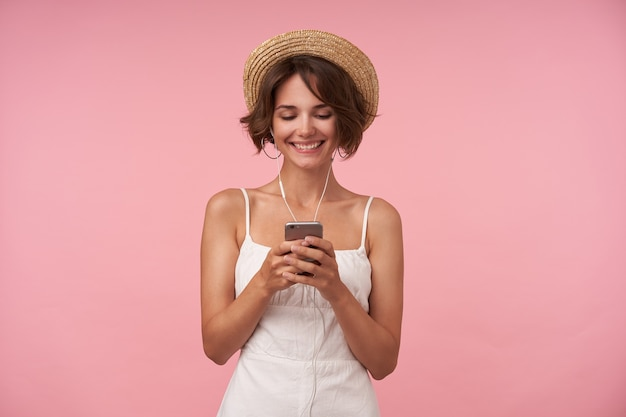 Cheerful lovely brunette female with casual hairstyle looking at screen of her phone and smiling broadly, typing message while listening to music with headphones, isolated