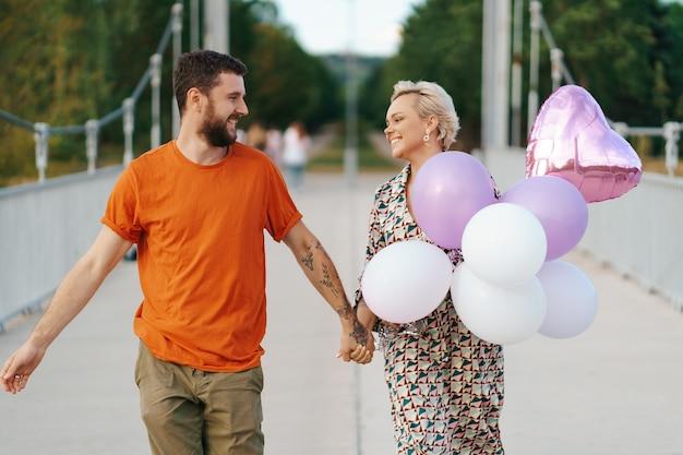 Coppie adorabili allegre che camminano felici sul ponte con il loro cane e palloncini rosa sorridenti