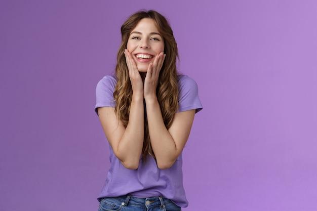 陽気で可愛くてかわいい笑顔の幸せな女の子がニヤリと笑って喜んでタッチ頬を楽しんで夏の暖かい日を楽しんで喜んで表情積極的な友情スタンド紫の背景。コピースペース