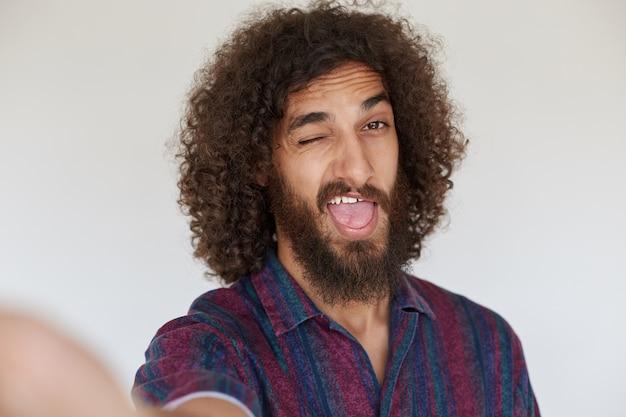 カジュアルな服装で額にしわを寄せ、口を大きく開けてウインクをしている青々としたあごひげを持つ陽気な素敵な黒髪の巻き毛の男