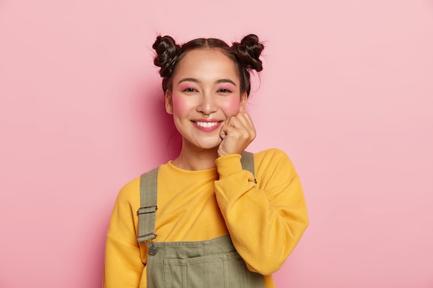 Cheerful lovely young asian woman with rouge cheeks, keeps one hand under chin, has two buns, wears yellow sweater and brown overalls