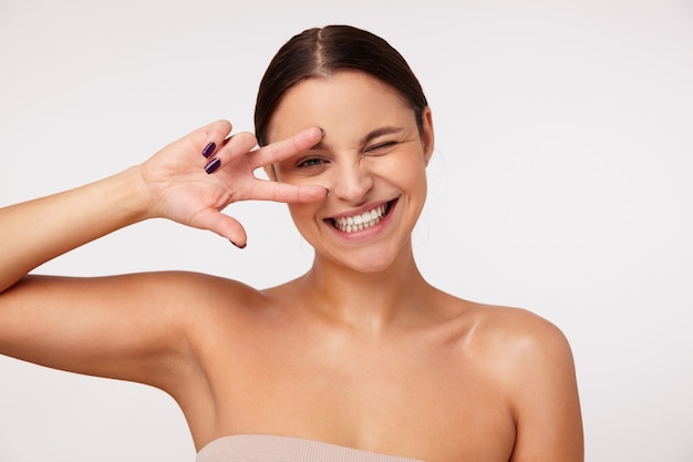 Cheerful lovely young brunette woman with casual hairstyle raising victory gesture to her face and keeping one eye closed while smiling happily, isolated