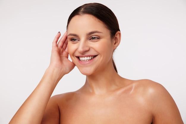 ポニーテールの髪型を持つ陽気な素敵な若いブルネットの女性は、彼女の耳の後ろに手を上げて、ポーズをとっている間幸せに笑っています