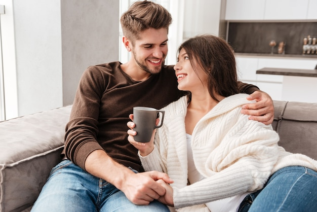Cheerful lovely young couple sitting and drinking coffee on sofa at home