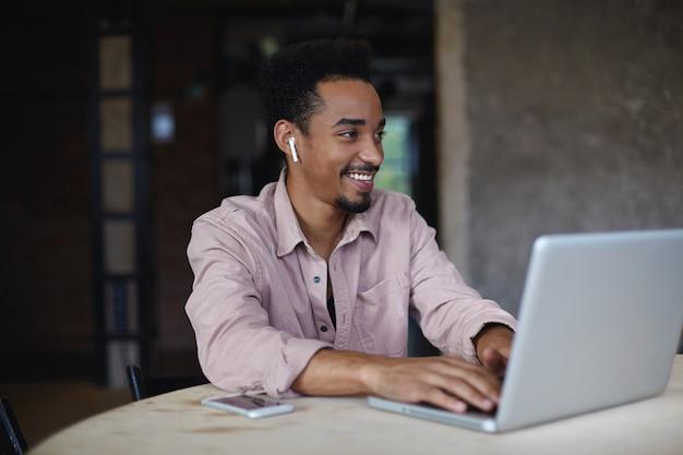 ベージュのシャツを着た短いヘアカットの陽気な素敵な若い暗い肌の男性は、ラップトップで現代のオフィスで働いて、キーボードで手でテキストを入力し、脇を見て、広く笑っています