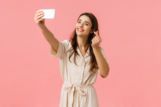 Cheerful lovely young european woman using filter to take cute selfie, photographing on mobile camera, smiling and showing korean heart gesture at smartphone, standing pink