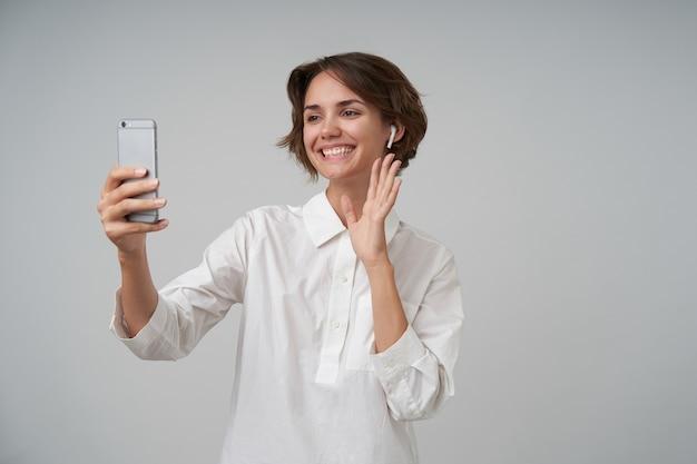 짧은 갈색 머리가 제기 손에 휴대 전화를 유지하고 웃고, 서있는 동안 흰 셔츠를 입고 쾌활한 사랑스러운 젊은 여성