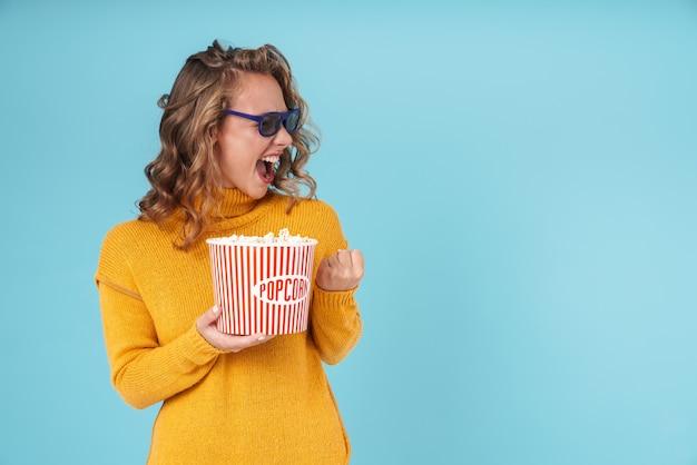 스웨터와 3d 안경을 쓴 쾌활하고 사랑스러운 소녀는 파란색으로 격리되어 영화를 보면서 팝콘을 먹습니다.