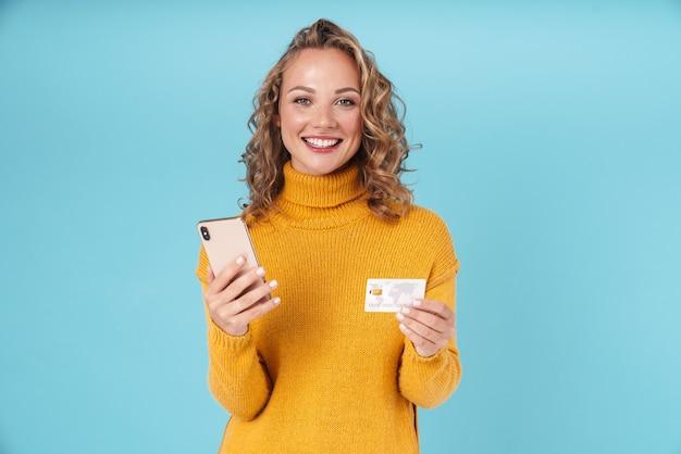 Веселая милая молодая девушка в свитере стоя изолирована на синем, используя мобильный телефон, показывая кредитную карту, делая покупки