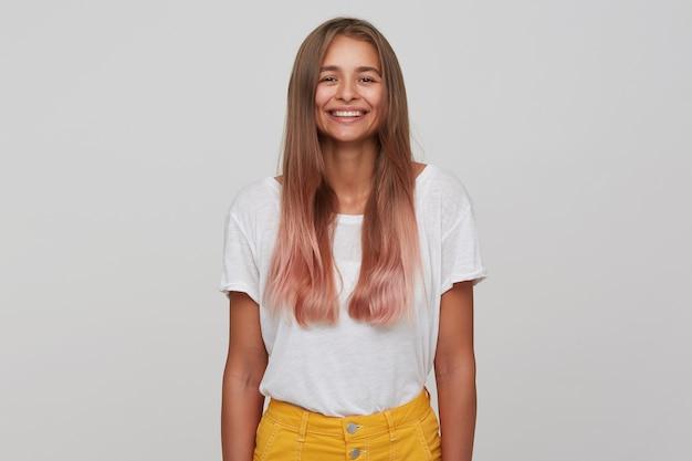 아래로 손으로 흰 벽 위에 포즈를 취하는 동안 흰색 기본 티셔츠와 노란색 치마를 입고 자연 화장과 쾌활한 사랑스러운 젊은 긴 머리 금발 아가씨