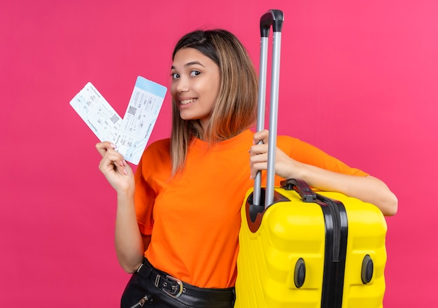 A cheerful lovely young woman in an orange t-shirt showing plane tickets with yellow suitcase on a pink wall
