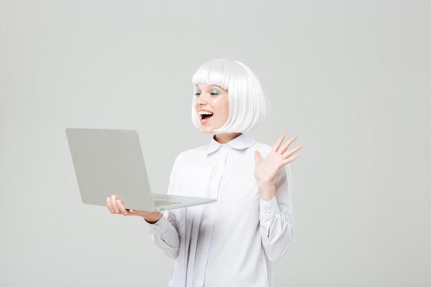 Веселая милая молодая женщина, стоящая и использующая ноутбук