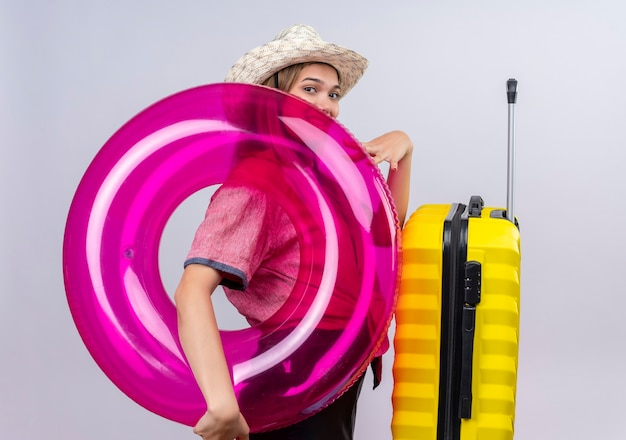Una giovane donna adorabile allegra che indossa camicia rossa e cappellino da sole guardando mentre si tiene l'anello gonfiabile con la valigia gialla su una parete bianca