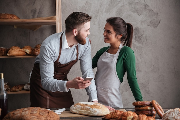 Cheerful loving couple bakers holding mobile phone.