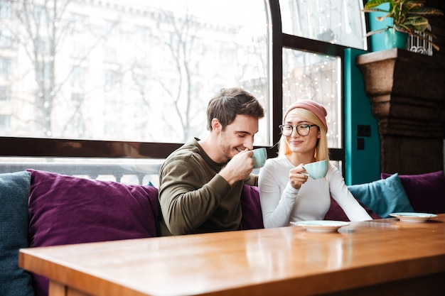 Cheerful loving couple sitting in cafe and drinking coffee.