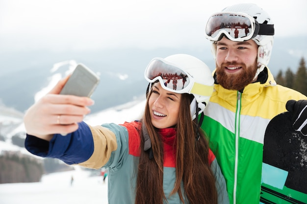 Cheerful loving couple snowboarders on the slopes frosty winter day making selfie by the phone