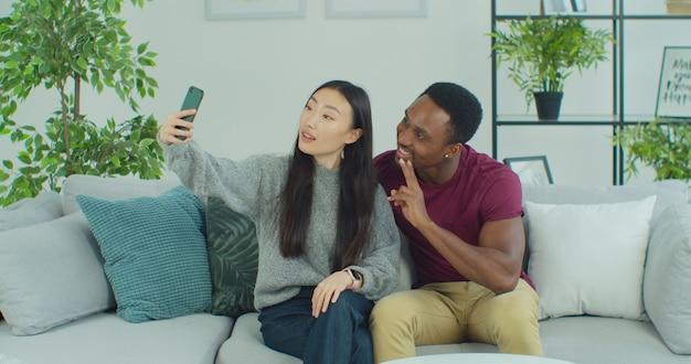 Веселая любящая пара смешанного этнического происхождения делает селфи на камеру смартфона дома
