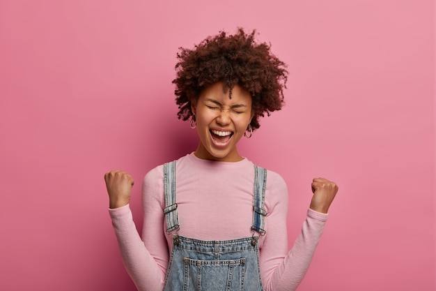 Cheerful lucky dark skinned model happy to achieve goal, clenches fists and exclaims with joy, becomes real champion, cheers over something, stands glad against pink wall. celebration.