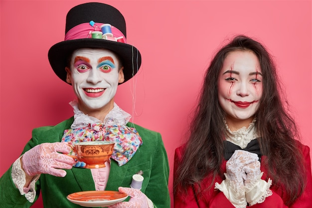 Cheerful mad hatter enjoys drinking hot tea looks with friendly expression at front. smiling brunette asian woman has scary makeup dressed on masquerade or carnival