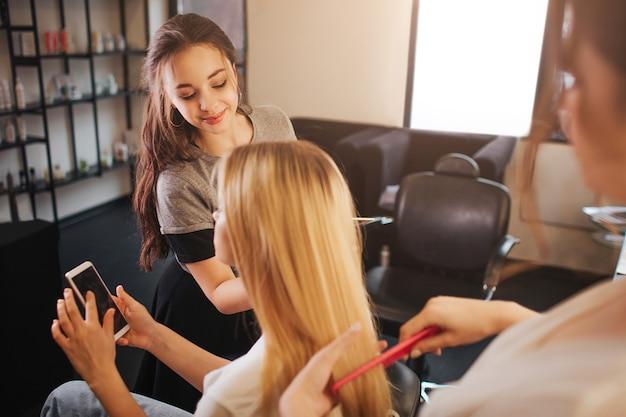 명랑 메이크업 아티스트 뷰티 룸에서 금발의 여자를 위해 확인합니다. 미용사는 뒤에서 일하고 금발 머리를 닦습니다. 클라이언트 보류 전화.