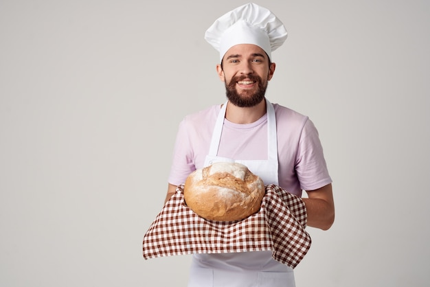 Cheerful male baker holding bread in hands preparing food light background