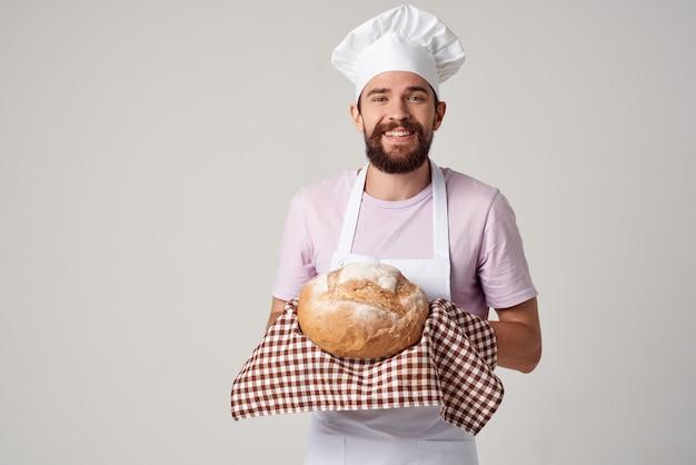 Веселый мужской пекарь держит хлеб в руках, готовит еду на светлом фоне