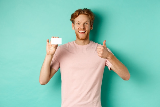 Cheerful male bank client in t-shirt showing thumb up and plastic credit card, smiling satisfied at camera, standing over turquoise background.