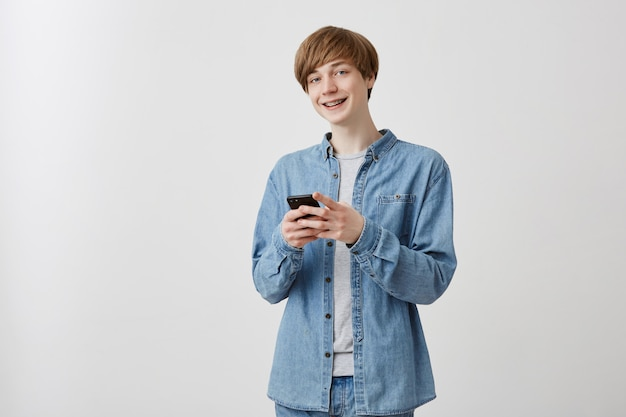 Cheerful male blogger with fair hair dressed in denim clothes, uses app on smart phone, enjoyes leisure at home. glad caucasian young male blogger shares ideas with followers, surfes website online.