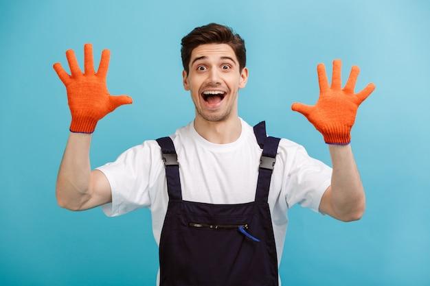Веселый мужчина-строитель показывает руки руками в перчатках над синей стеной