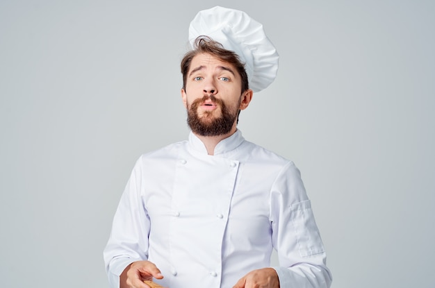 Веселый мужской шеф-повар готовит еду на кухне, ресторан работает профессионально