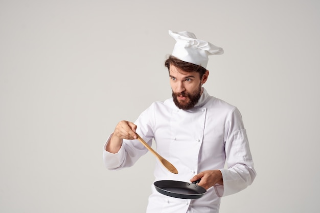 Cheerful male chef frying pan in hands cooking food professional cooking