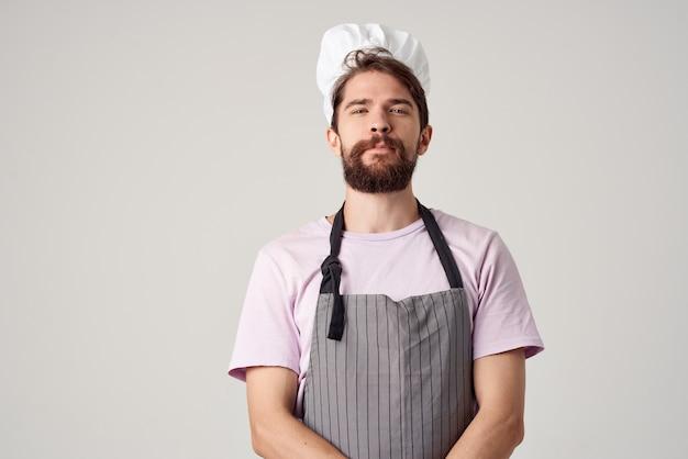 Веселый шеф-повар-мужчина в униформе, работающей на профессиональной кухне