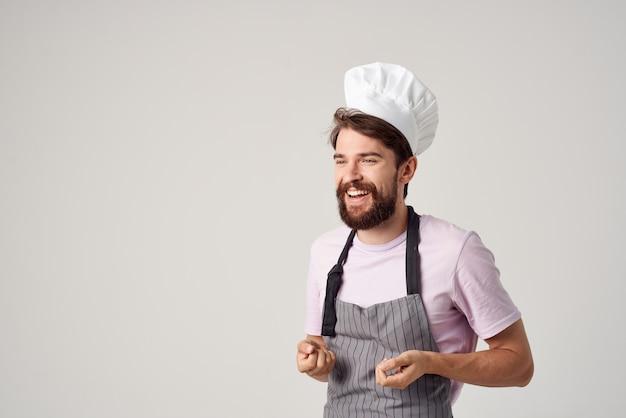 食品を扱う陽気な男性シェフのキッチンの専門家